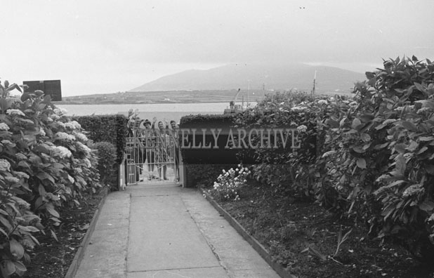 1953; A Group Of Men Waving At The Gate Of The Royal Hotel On Valentia Island.