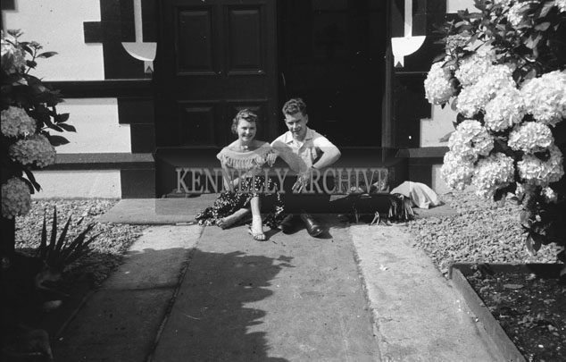 1953; A Couple Sitting On The Steps Outside The Royal Hotel On Valentia Island.