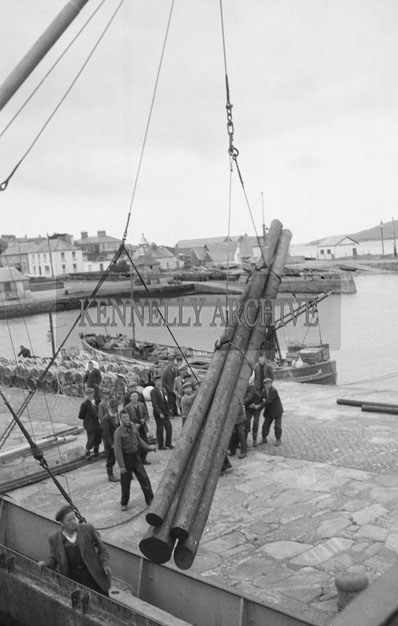 1953; A Photo Of A Crane Lifting Pipes With A Crew Of Men Assisting At Valentia Pier.