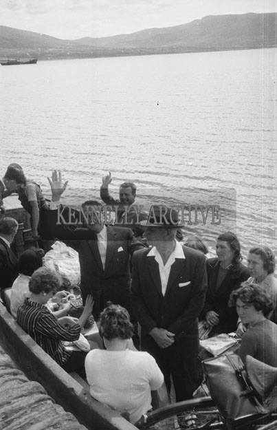 1953; Television star Eamonn Andrews (at back) with a group on in a boat Valentia Island.