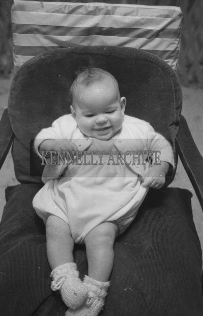 1953; A Studio Photo Of A Baby Sitting In A Chair.