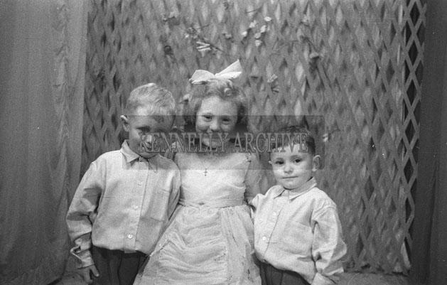 1953; A Studio Photo Of Three Young Children.