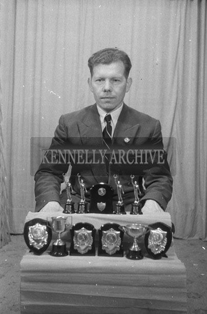 1953; A Studio Photo Of A Man Posing With His Trophies.