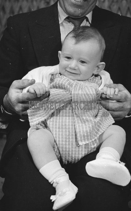 1953; A Studio Photo Of A Father Holding His Baby.