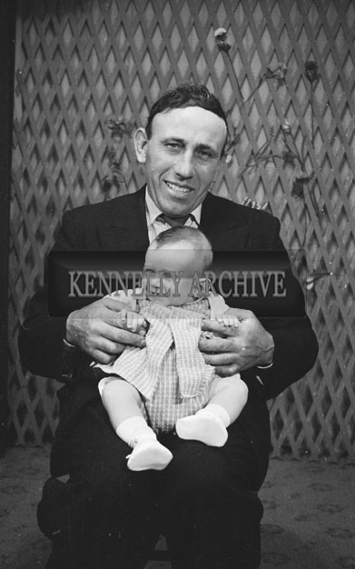 1953; A Studio Photo Of A Father And His Baby Posing For The Camera.