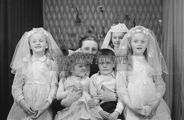 1953; A Studio Photo Of Twin Girls And Another Girl Dressed In Their Communion Dresses Posing For The Camera With Family Members.