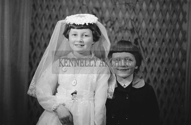 1953; A Studio Photo Of A Communion Girl Posing For The Camera With A Family Member.