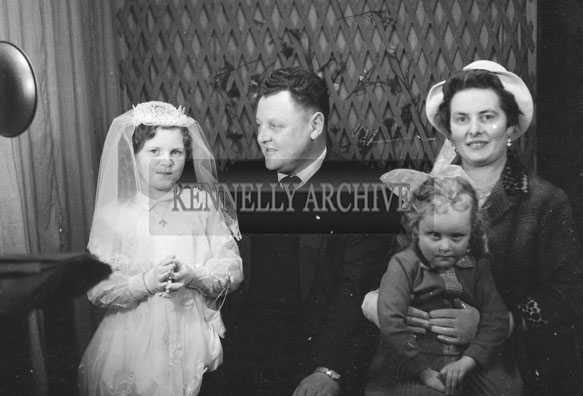 1953; A Studio Photo Of A Communion Girl Posing For The Camera With Her Family.