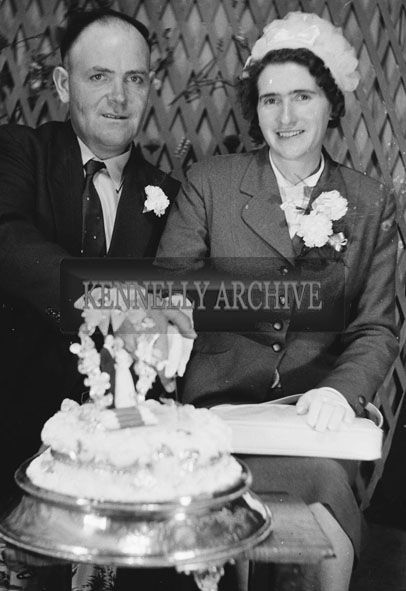 1953; A Studio Photo Of A Bride And Groom Posing For The Camera With Their Wedding Cake.