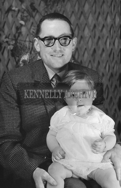 1953; A Studio Photo Of A Father Holding His Baby Girl.
