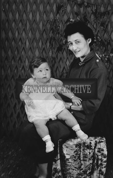 1953; A Studio Photo Of A Mother Holding Her Baby Girl.