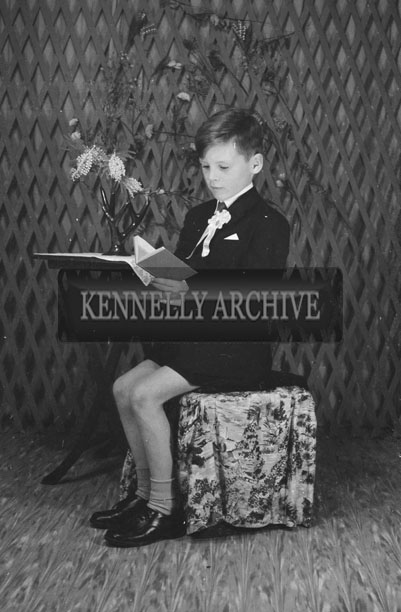 1953; A Studio Photo Of A Communion Boy Reading.