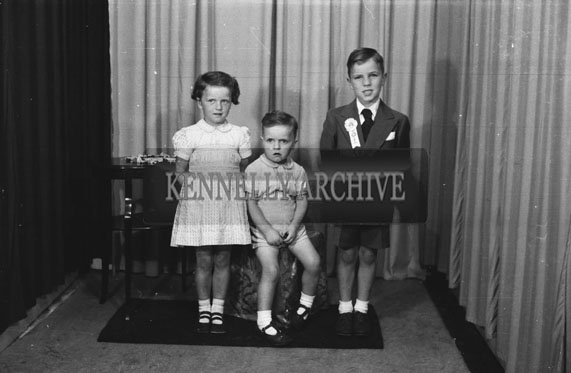 June 1954; A Studio Photo Of A Communion Boy And His Family.