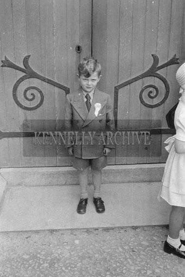 June 1954; A Photo Of A Communion Boy Standing At A Church Door.