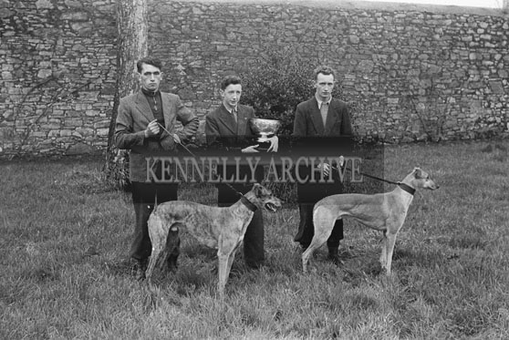 December 1953; A Group Of Men With A Trophy And Their Greyhounds.