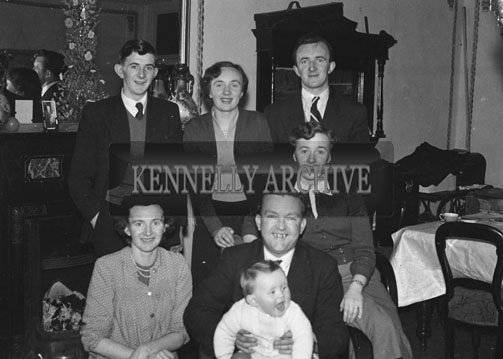 November 1954; A family celebrating a Baby's First Birthday at home. Derry O'Rourke is standing at the back on the right.