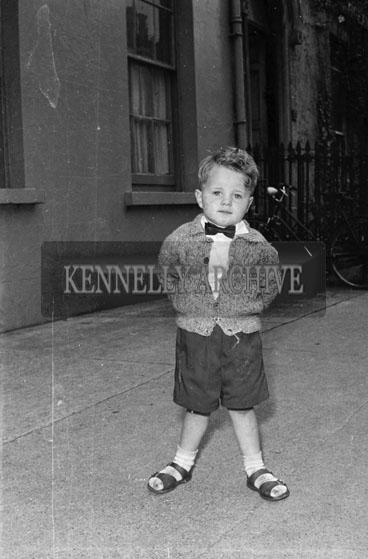1956; A photo of a young boy taken outside.