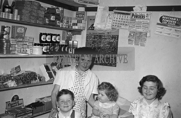 1956; A photo taken of a family in a shop at an unknown location in Kerry.