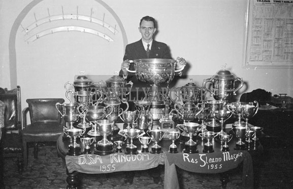 January 1956; Padraig Kennelly Senior holding the Sam Maguire behind a display of the National Champions of Kerry Trophies In Tralee.