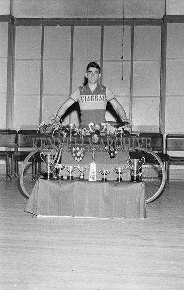 1956; A member of the Kingdom Cycle Club poses for the camera with his bike and is surrounded by trophies.