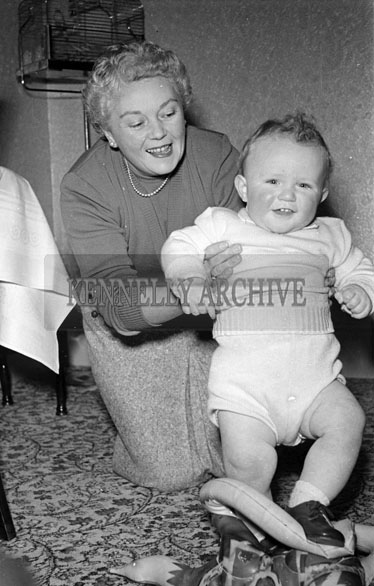 November 1956; A photo of the McCann Baby and two people take at home on its First Birthday.