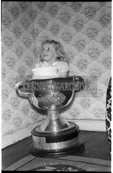 June 1956; A photo of a girl in the Sam Maguire Cup taken at home.