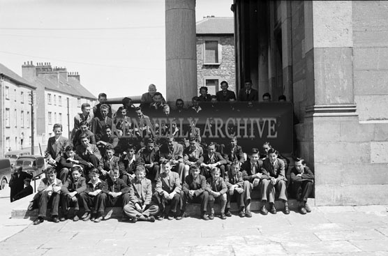 June 1956; Pupils from Tralee Technical School pose for the camera outisde the Court House in Tralee.