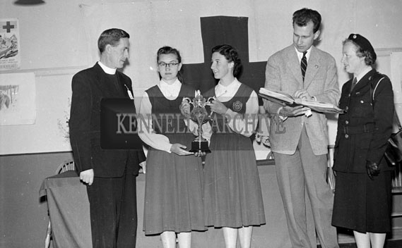 9th July 1956; Two girls after receiving an award at the Irish Junior Red Cross Conference which took place in Tralee pictured with a woman and two gentlemen.