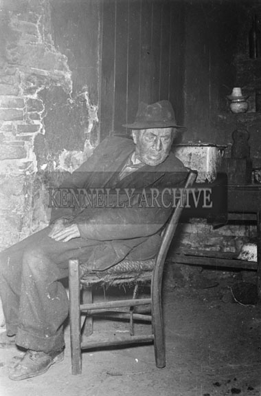 1956; A photo of an old man sitting on a chair at an unknown location in Kerry.