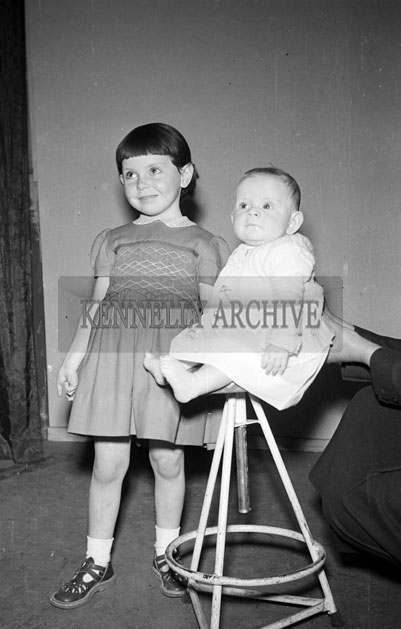 May 1957; A studio photo of a baby and a young girl.