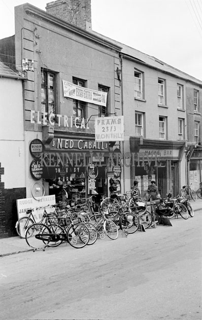 May 1957; A photo of Ned Caball's Bicycle Shop and Mack's Bar.