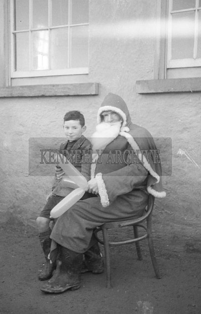 December 1957; A photo of Santa with a student at Murhar National School, Moyvane.