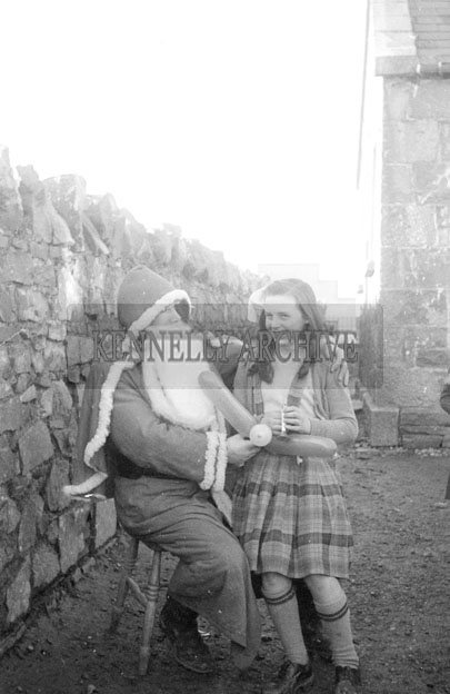 December 1957; A photo of Santa with a student at Tarbert National School.