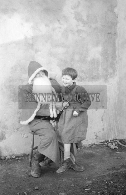 December 1957; A photo of Santa with a student outside Abbeyfeale Convent School.
