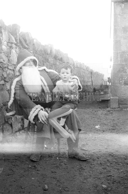 December 1957; A photo of Santa with a young boy at Tarbert National School.