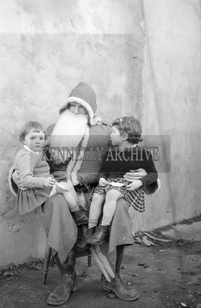 December 1957; A photo of Santa with two students outside Abbeyfeale Convent School.