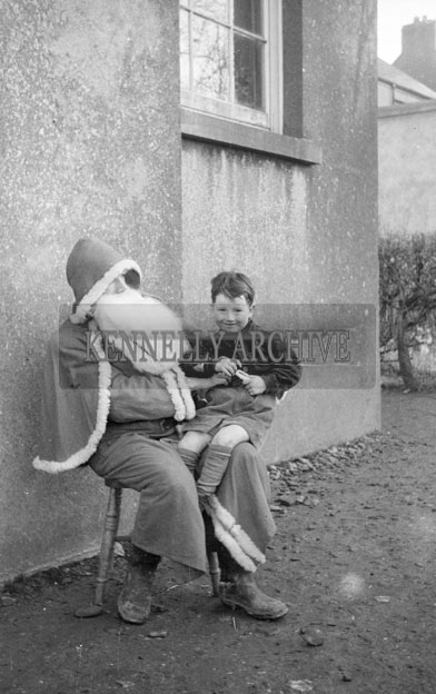 December 1957; A photo of Santa with a student at Abbeyfeale Boys National School.