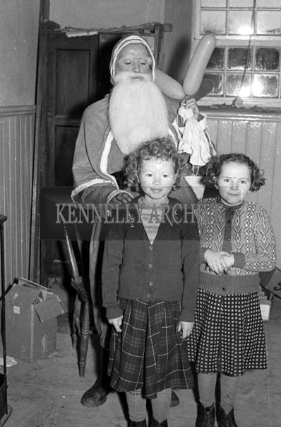 December 1957; A photo of Santa with two students at a National School near Abbeyfeale.