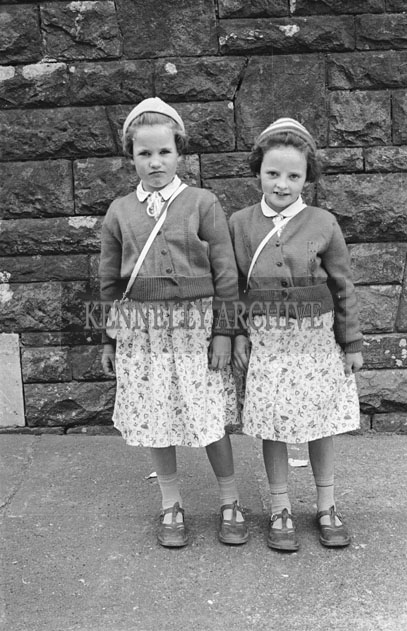 6th May 1957; Two girls pose for the camera on confirmation day in Dingle.