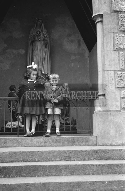 May 1957; A young boy and girl stand on the steps of the Grotto in Dingle.