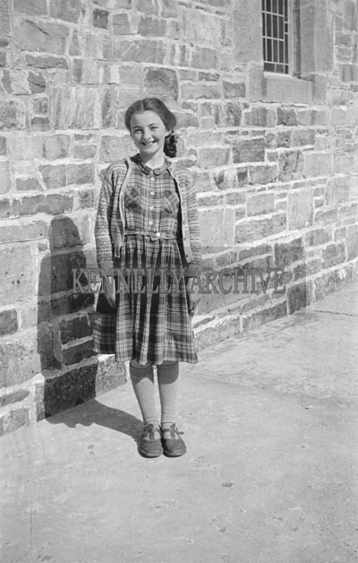 May 1957; A girl poses for the camera in the Chuchyard at Glenbeigh.