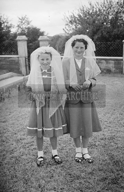 6th May 1957; Two girls smile for the camera on their confirmation day in Annascaul.