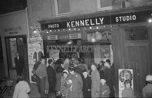 December 1957; Children queue to see Santa Claus outside Padraig Kennelly's photo studio, Ashe Street, Tralee.