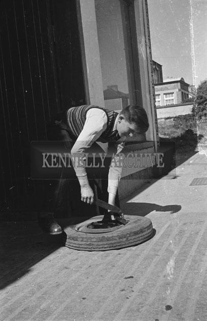 June 1957; A Mechanic fixes a tyre in Tobin's Garage, Abbeyfeale.