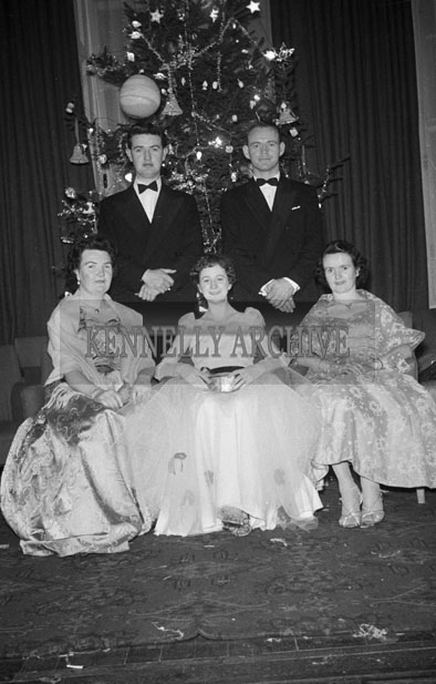 27th December 1957; A group of people posing for the camera at Tralee Rugby Club Dress Dance in The Great Southern Hotel, Killarney.