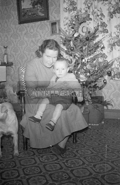 December 1957; A photo of a baby and his grandmother, taken in his home.
