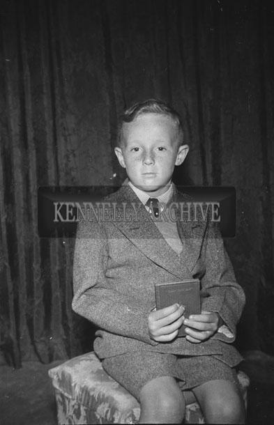 June 1957; A studio communion photo of a boy.