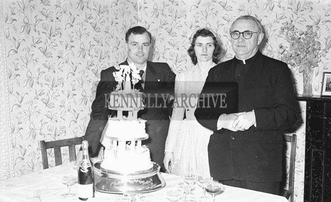 February 1957; A photo of a wedding party in a house.
