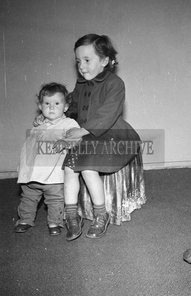 August 1957; A studio photo of a young girl and boy.