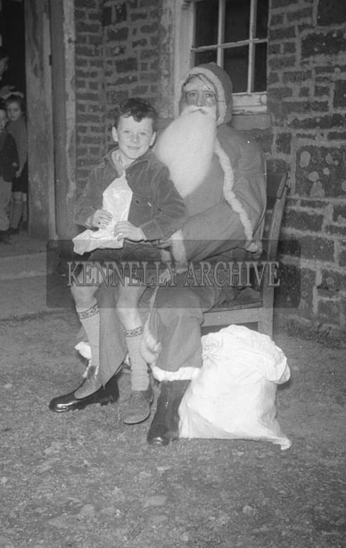 December 1957;  A photo of Santa outside a school with a student.